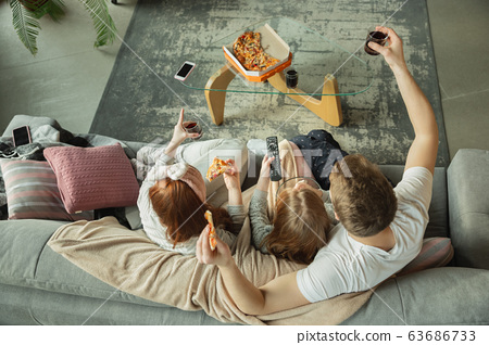 Family spending nice time together at home, looks happy and cheerful, eating pizza. Top view. 63686733