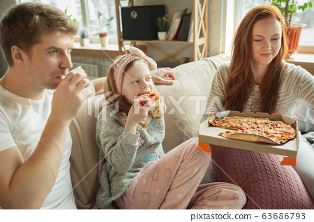 Family spending nice time together at home, looks happy and cheerful, eating pizza 63686793
