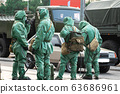 People in bio viral hazard protective suits. Disinfection and decontamination on a public place as a 63686961