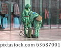 People in bio viral hazard protective suits. Disinfection and decontamination on a public place as a 63687001