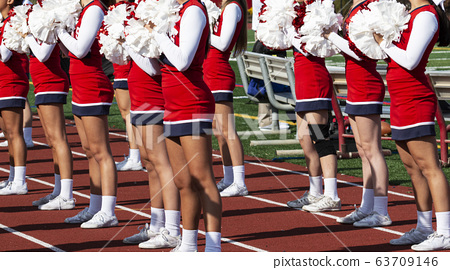 Cheerleaders with pom poms cheering at high school 63709146