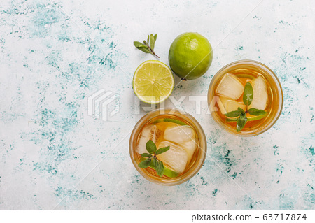 Iced tea with lime and ice on light background 63717874