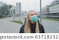 Concerned woman in medical coronavirus mask walking on the street 63718232