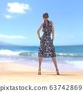 หญิงสาวในชุดฤดูร้อนยืนอยู่บนชายหาดที่มีภาพประกอบวัสดุ 3DCG 63742869