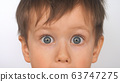 Baby with big eyes, surprised look. Boy with funny amazed expression, close-up 63747275