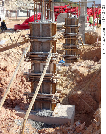 KUALA LUMPUR, MALAYSIA -MARCH 13, 2020: Column timber form work and reinforcement bar at the construction site. Installed by construction workers. The structure supported by temporary wood support. 63748803
