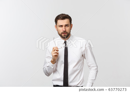A handsome young Caucasian millennial man in glasses and a white T-shirt isolated on a gray studio background, looks at blank copy. 63770273