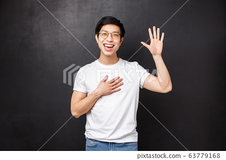 Informal greeting concept. Outgoing attractive young asian guy introduce himself in front of team, raise hand and pointing at him as saying own name, smiling hello gesture, black background 63779168