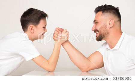Playful dad and son compete in arm wrestling 63786986