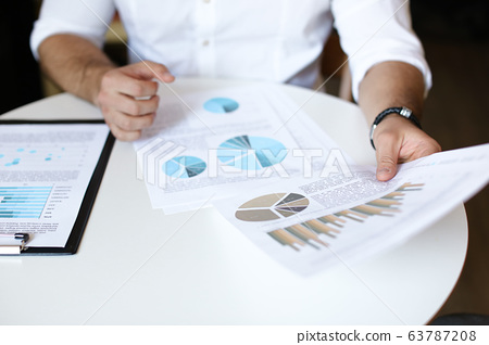 Male person working with documents and diagrams. 63787208