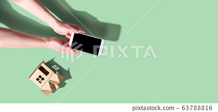 Person using a smartphone with a miniature house 63788816