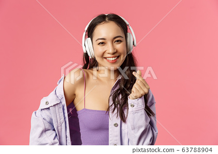Close-up portrait of attractive happy young modern asian girl, listening music in headphones, show korean heart sign, enjoying favorite music or podcast, bought earphones with discount 63788904