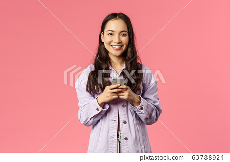 Online lifestyle, people and beauty concept. Cheerful stylish young girl using mobile phone and smiling pleased at camera, chatting during lockdown, use education app, pink background 63788924