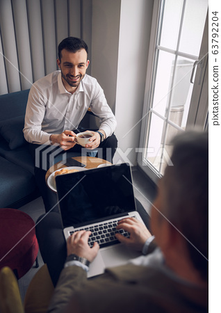 Smiling businessman typing on keyboard of laptop 63792204