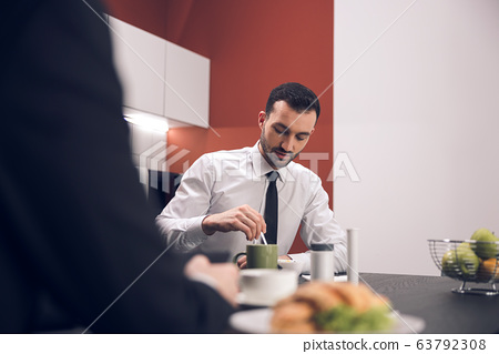 Caucasian young man drinking tea in office 63792308