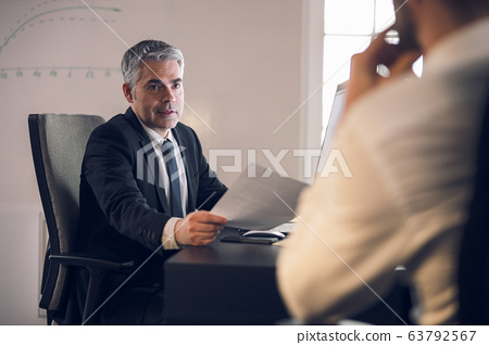 Mature boss keeping documents in arm at his workplace 63792567