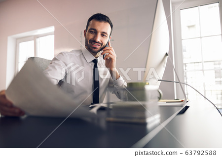 Caucasian man talking on smartphone in the office 63792588