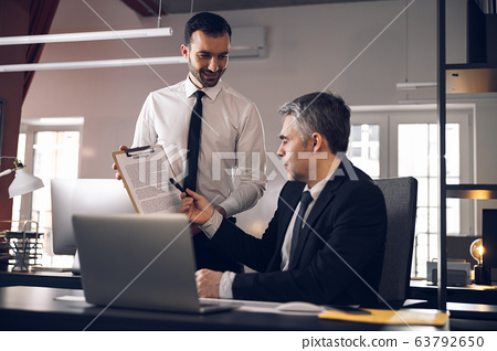 Mature boss in suit signing papers in office 63792650