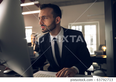 Caucasian serious man looking at screen of computer attentively 63792713