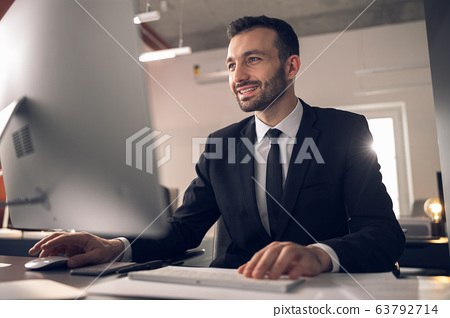 Caucasian young man looking at screen of gadget attentively 63792714