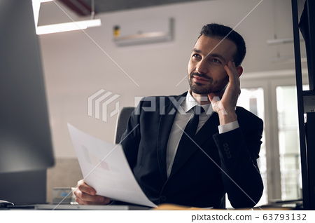 Handsome businessman is reading documents in office 63793132