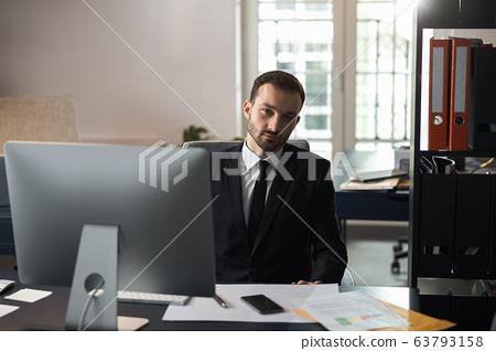 Caucasian businessman posing for camera in office 63793158