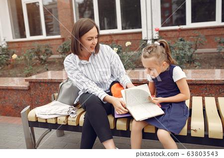 Mother prepare little daughter to school 63803543