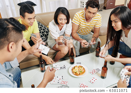 Friends playing cards at home 63811071