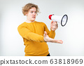 blond wavy man shouting news in a megaphone on a white studio background 63818969