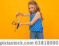 teenager girl breaks glasses in hands on a yellow background with copy space 63818990