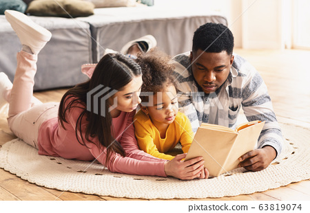Multiracial family looking at book, stay at home 63819074