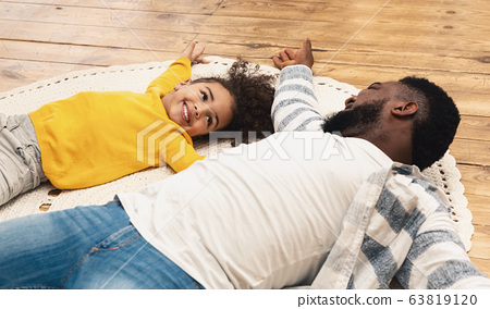 Smiling african american father and daughter staying home 63819120