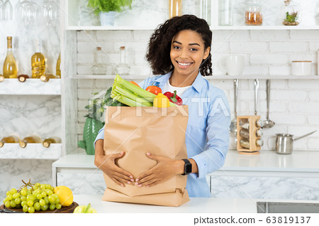 Satisfied afro girl holding paper bag with food 63819137