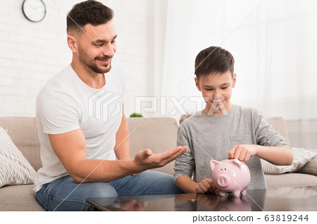 Dad teaching his son to save money at home 63819244