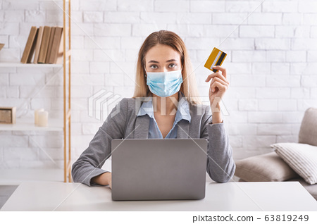 Woman in protective mask with laptop and credit card 63819249