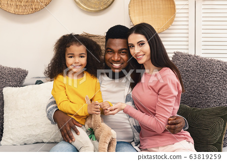 International parents play with their little girl 63819259