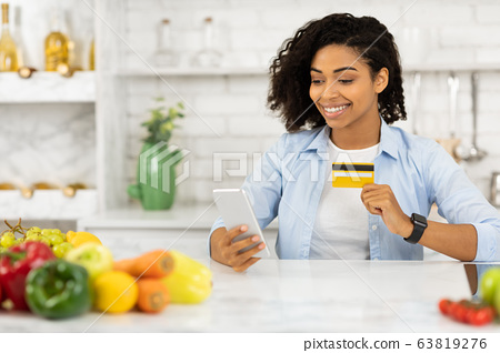Black girl using cell phone and credit card in the kitchen 63819276