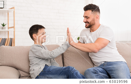 Father and son giving high five to each other at home 63819596