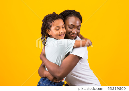 Black mother hugging with her happy girl 63819800
