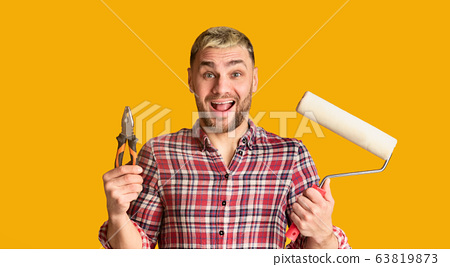 Guy holds pliers and roller in his hands 63819873