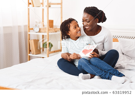 Afro kid congratulating her mom sitting on the bed 63819952