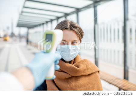 Measuring temperature of a young woman in face mask at a checkpoint outdoors 63823218