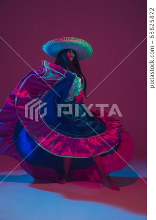 Fabulous Cinco de Mayo female dancer on purple studio background in neon light 63825872