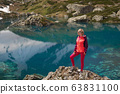 Hiking woman in red jacket stay at beautiful lake in mountains. 63831100