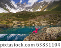Hiking woman in red clothes sitting at beautiful turquoise lake in mountains. 63831104