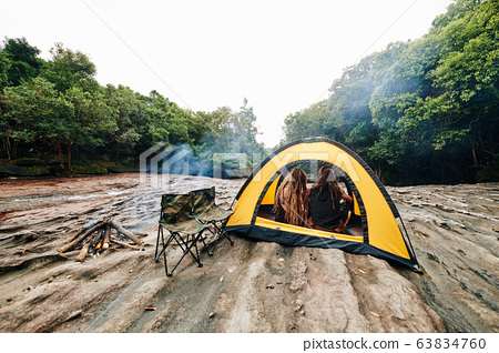 Couple sitting in tent 63834760