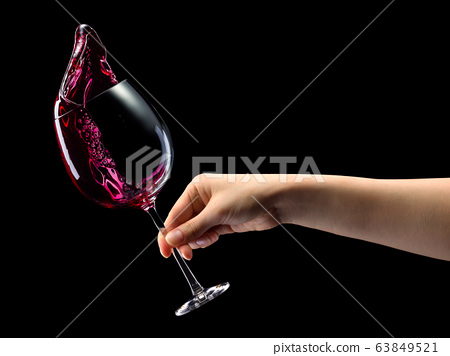 Woman hand holding red wine glass with splashes 63849521