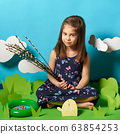 girl sits next to Easter eggs on green paper decoration 63854253