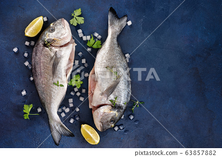 Two raw dorado fishes with herbs and lemon on dark 63857882