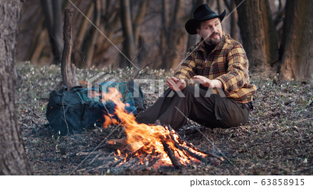 Outdoorsman warming hands from campfire 63858915